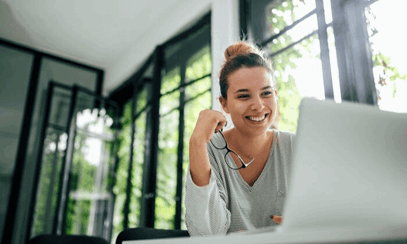 Woman smiling and working at laptop in office