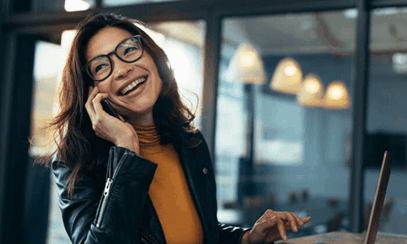 Professional woman smiling and taking call on mobile phone at desk