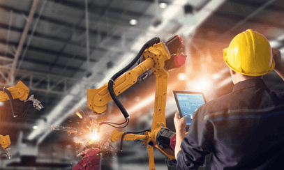 Man watching manufacturing machinery using AI on tablet