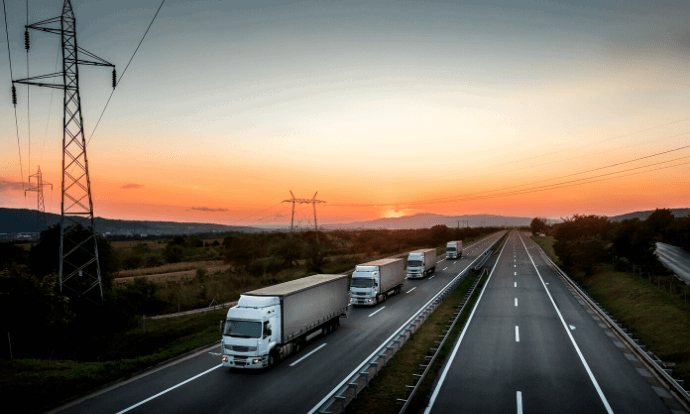 Lorries driving in a line on motorway during sunset