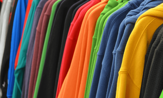 Hooded tops on hangers in lots of different colours