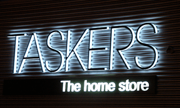 Taskers PLC logo on side of building