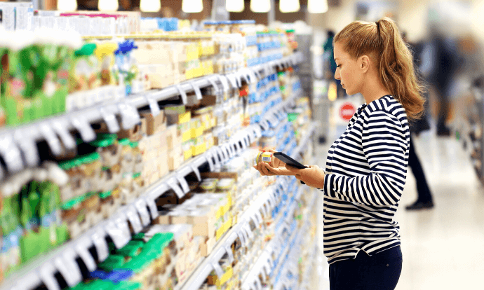 Woman analysing product on shelf at supermarket